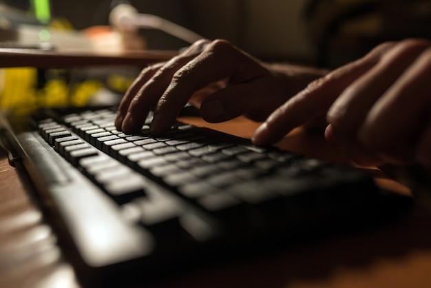 Finger drücken auf eine computertastatur in der dunkelheit.