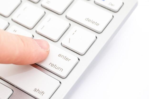 Finger drückt den knopf der weißen tastatur auf weiß.