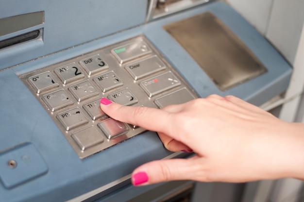 Finger drückt die passwortnummer auf dem geldautomaten