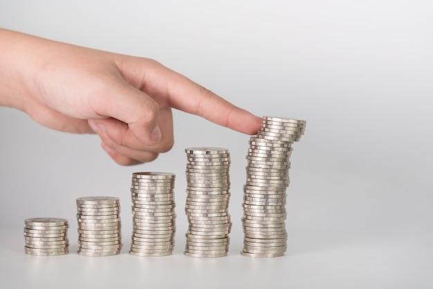 Finger drückt einen haufen münzen
