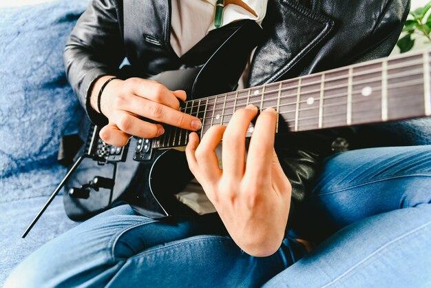 Finger eines gitarristen auf den bund des mastes der gitarre gelegt, der einen akkord spielt, der das klopfen tut.