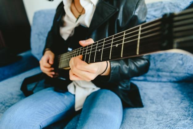 Finger eines gitarristen, der auf dem bund des gitarrenmastes platziert ist und einen akkord beim tapping spielen.