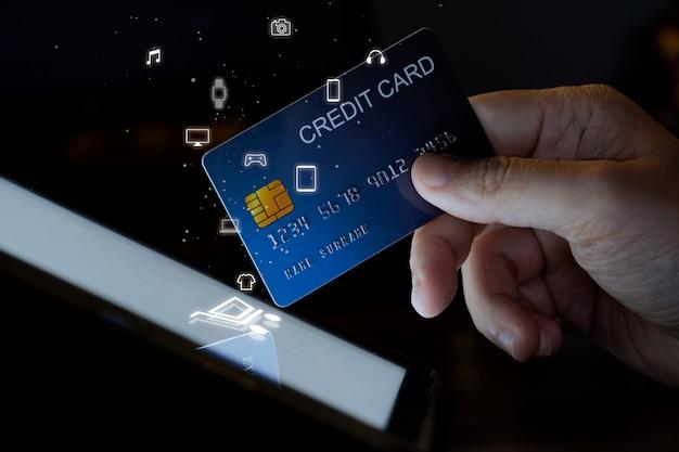 Finger halten kreditkartenberührung auf tablet-bildschirm mit einkaufssymbol. konzept für online-shopping handy-technologie und gerät.