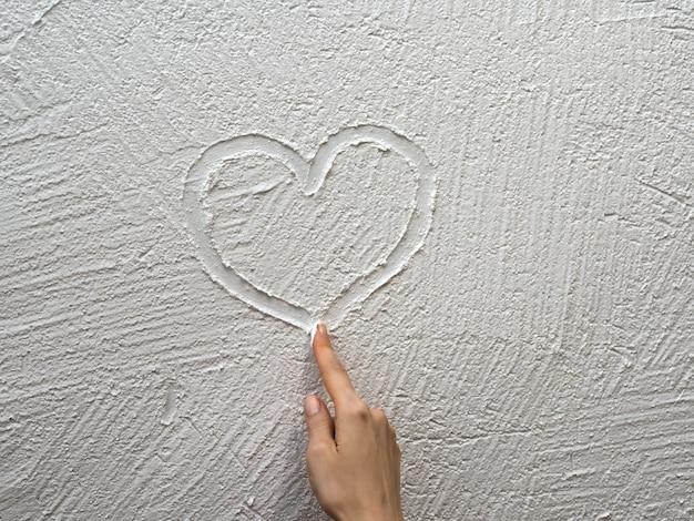 Finger malt ein herz auf eine weiße stuckwand. valentinstag konzept.
