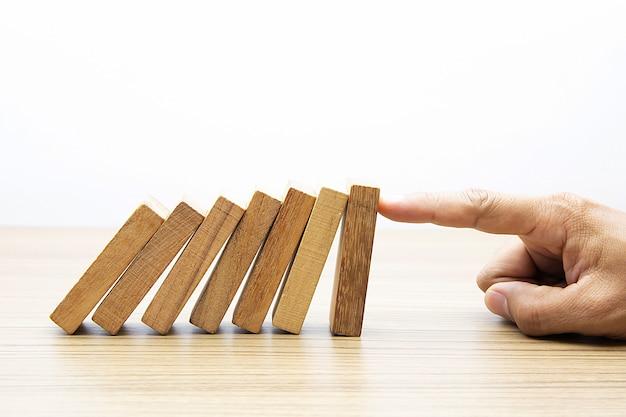 Finger stoppen hölzernen domino.