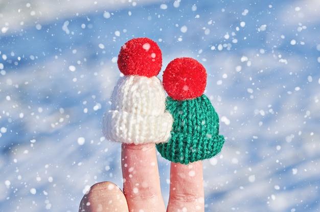 Fingergesichter in den woolen hüten gegen blauen winterhintergrund der schneeflocke. glückliche familie, die konzept für weihnachten oder neujahr feiert