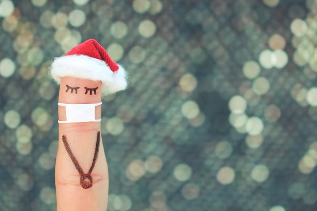 Fingerkunst der einsamen frau in der medizinischen maske von covid-2019. konzeptleute feiern weihnachten im neujahrshut.