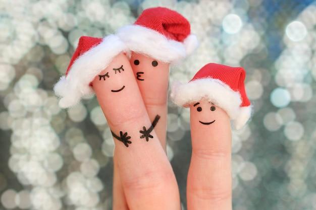 Fingerkunst der familie feiert weihnachten. konzept der gruppe von personen lächelnd in den hüten des neuen jahres.