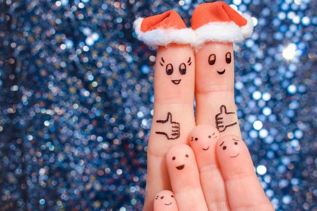 Fingerkunst der großen familie feiert weihnachten. konzept der gruppe von personen lachend in den hüten des neuen jahres. glückliches paar, das sich daumen zeigt.