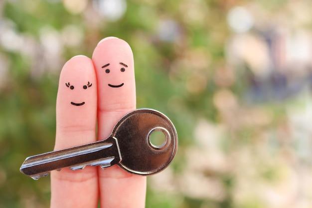 Fingerkunst des glücklichen paares. familie hält hausschlüssel.