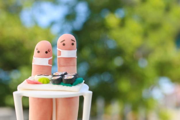 Fingerkunst des glücklichen paares in medizinischer maske von covid-2019. mann und frau essen sushi im café.