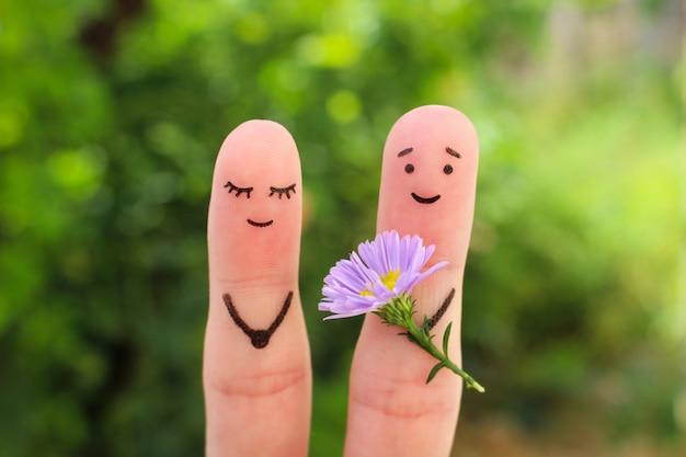 Fingerkunst des glücklichen paars. mann gibt der frau blumen.