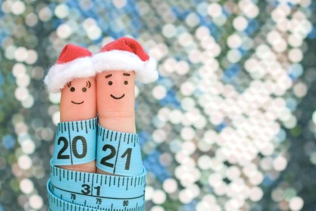 Fingerkunst des paares feiert weihnachten. konzept von mann und frau, die in neujahrshüten lachen. maßband ist 2021 geschrieben.