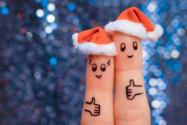 Fingerkunst des paares feiert weihnachten. mann und frau, die in den hüten des neuen jahres lachen. glückliches paar, das sich daumen zeigt.