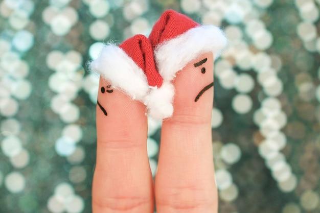 Fingerkunst des paares feiert weihnachten. paar nach einem streit in verschiedene richtungen schauen.