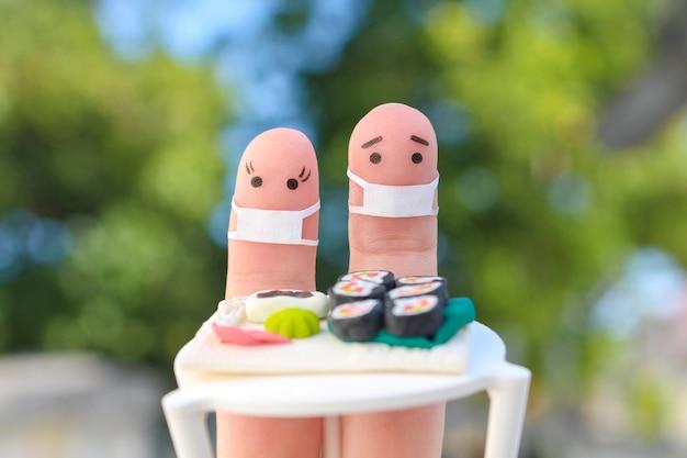 Fingerkunst des paares in medizinischen masken, die sushi essen