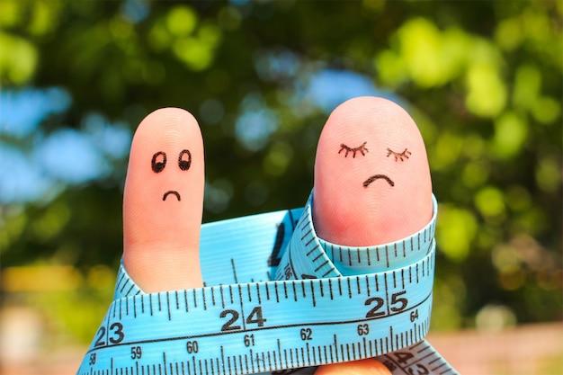 Fingerkunst des paares mit meter. das konzept mann ist dünn, frau ist fett.
