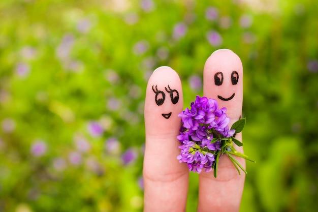 Fingerkunst eines glücklichen paares. mann gibt einer frau blumen.