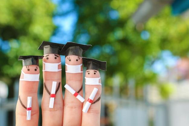 Fingerkunst von studenten in medizinischer maske von covid-2019. absolventen, die ihr diplom nach dem abschluss halten.