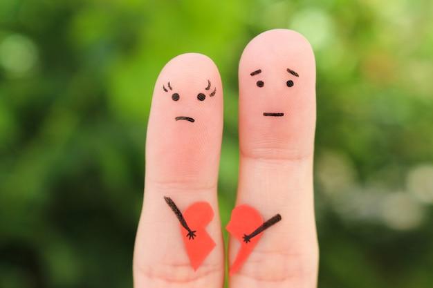 Fingerkunst von traurigen paaren. frau und mann, die defektes herz halten.