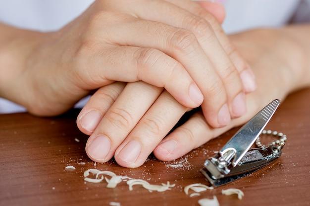Fingernägel einer frau, die mit einem nagelknipser nägel zu kurz schneidet. das konzept der pflege, saubere fingernägel.