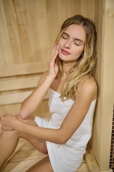Finnische sauna. eine blonde frau sieht entspannt aus, während sie in der finnischen sauna sitzt