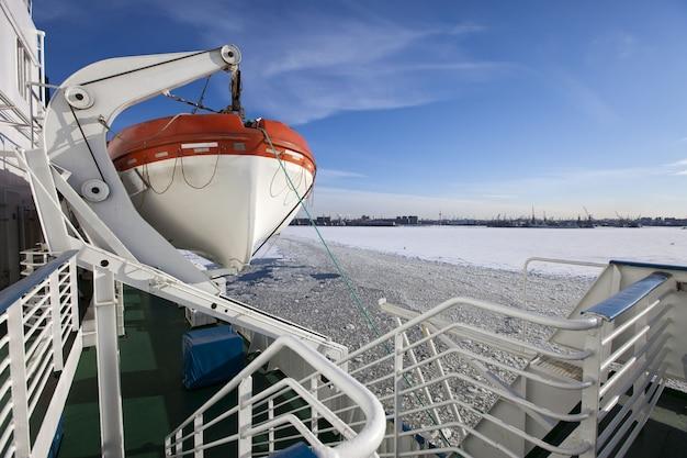 Finnischer meerbusen bedeckt mit eis am seehafen von st. petersburg und einem rettungsboot von einem schiff im vordergrund. russland