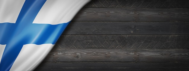 Finnland flagge auf schwarzer holzwand. horizontales panorama-banner.