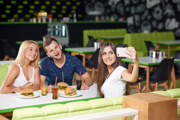 Firma, die telefon betrachtet und selfie im café nimmt