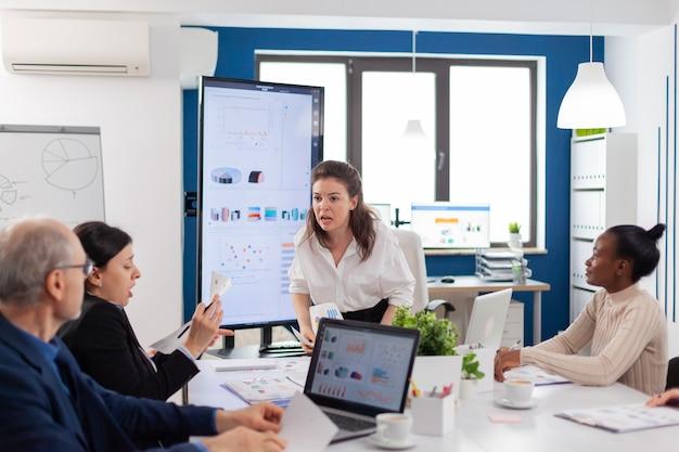 Firmenchef schreit leitenden angestellten während des treffens im konferenzraum an