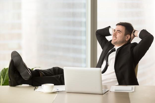 Firmendirektor, der am arbeitsplatz im büro sich entspannt