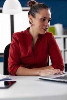 Firmendirektor, der dokumente auf laptop durchsieht