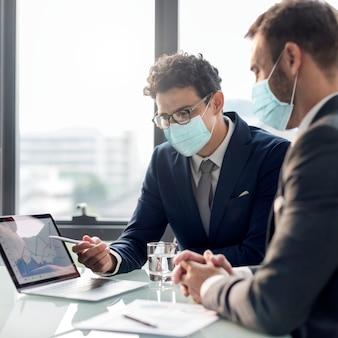 Firmengeschäftsleute in der gesichtsmaske, die in einem büro neu normal arbeitet