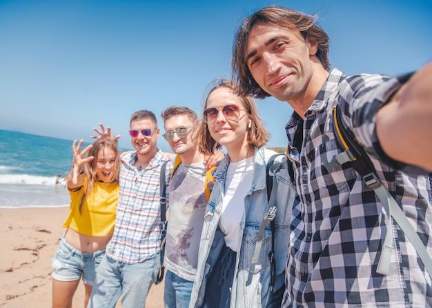 Firmengruppe der glücklichen umarmung junger hübscher leute, studentenmänner und -frauen an einem sonnigen strand, urlaubsreisefreundschaftstagkonzept