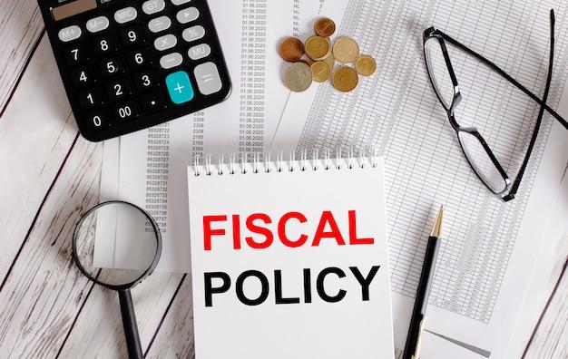 Fiscal policy geschrieben in einem weißen notizblock in der nähe eines taschenrechners, bargeld, brille, lupe und stift