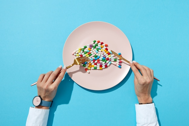 Fisch aus bunten pillen und tabletten auf einem weißen teller mit mädchenhänden mit uhr auf einer blauen wand mit schatten, kopierraum. draufsicht. bunte nahrungsergänzungspillen.