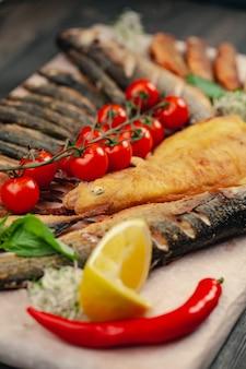 Fisch gegrillt auf einem teller mit gemüse und zitrone