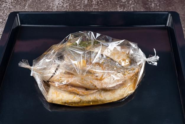 Fisch im backbeutel. dorado-fisch mit reis, sauce und kräutern in einer backhülle im kochfertigen ofen. mediterrane küche, europäisches gericht.