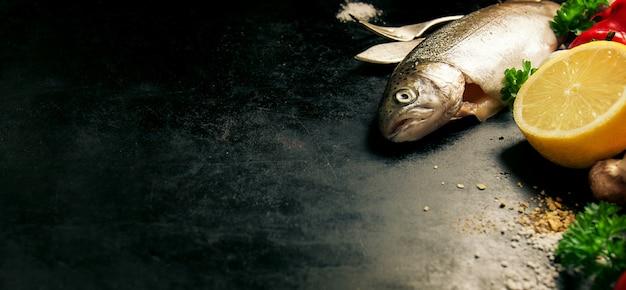 Fisch mit einer zitrone neben ihm auf einem schwarzen hintergrund