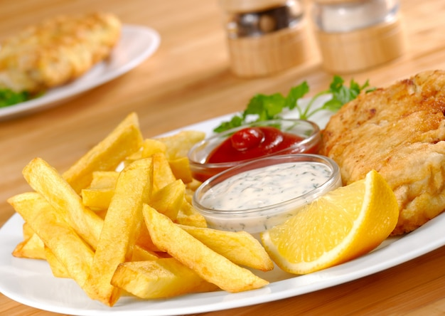 Fisch, pommes, mayo und ketchup auf weißem teller