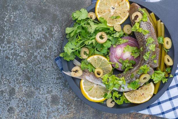 Fisch und gemüse auf einer holzpfanne, auf einem geschirrtuch.
