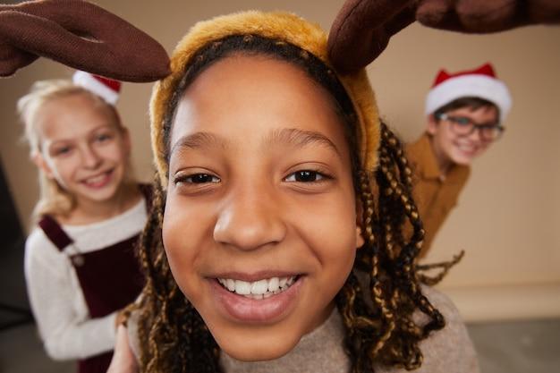 Fischaugenporträt von drei kindern, die weihnachtsporträts tragen und an der kamera lächeln, während sie gegen sein hintergrund im studio stehen