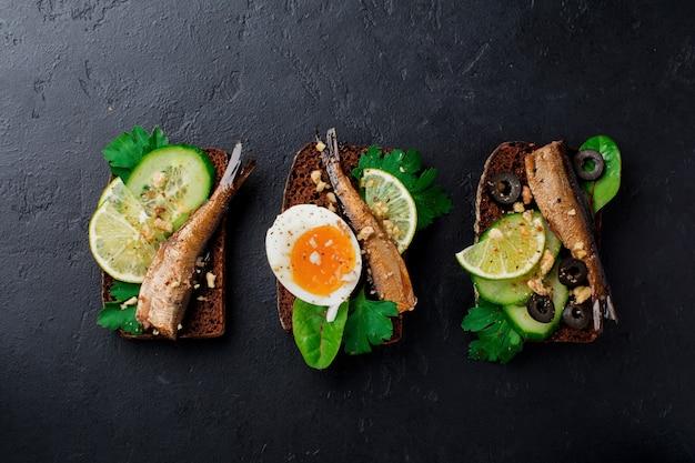 Fischbrötchen mit sprotten, gurke, limette, gekochten eiern, petersilienblättern und mangold auf roggenbrot auf schwarzer alter betonoberfläche. selektiver fokus