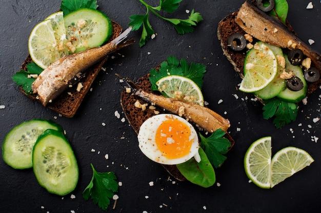 Fischbrötchen mit sprotten, gurke, limette, gekochten eiern, petersilienblättern und mangold auf roggenbrot