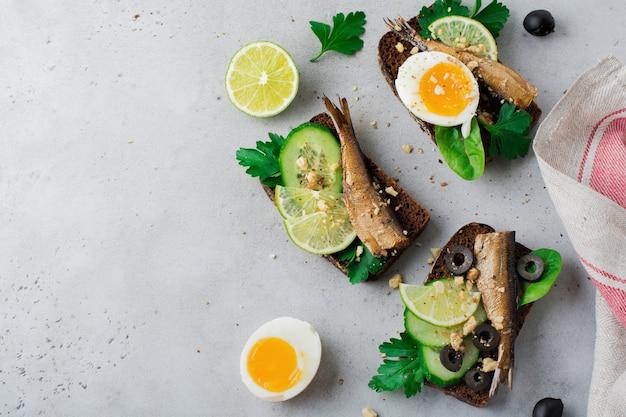 Fischbrötchen mit sprotten, gurke, limette, gekochten eiern