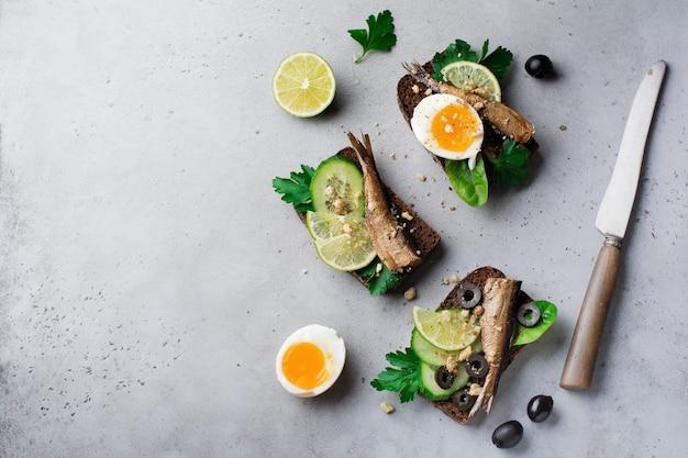 Fischbrötchen mit sprotten, gurken, limetten, gekochten eiern, petersilienblättern und mango auf roggenbrot auf einer grauen alten betonoberfläche. selektiver fokus