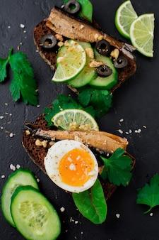 Fischbrötchen mit sprotten, gurken, limetten, gekochten eiern, petersilienblättern und mangold auf roggenbrot auf schwarzer alter beton- oder steinoberfläche