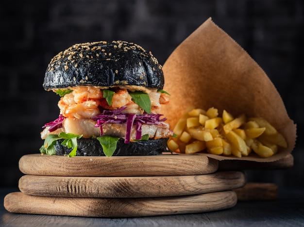 Fischburger mit garnelen und frischem salat. meeresfrüchte-burger in einem schwarzen brötchen