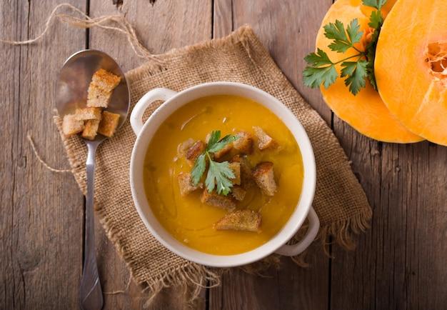 Fischcremesuppe mit lachs, käse, kartoffeln und kräutern in weissen suppentassen.