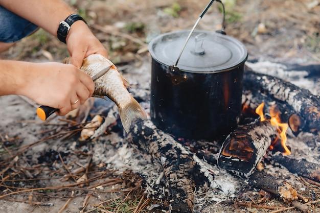 Fische für fischsuppe in der natur nahe feuer säubern und schneiden